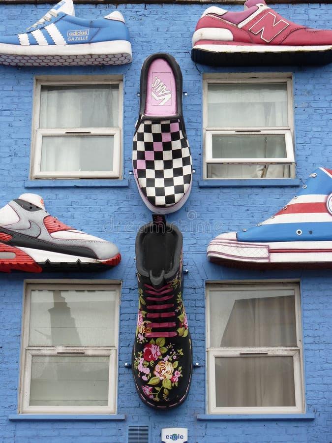 Una parete blu con i carichi delle scarpe immagine stock libera da diritti