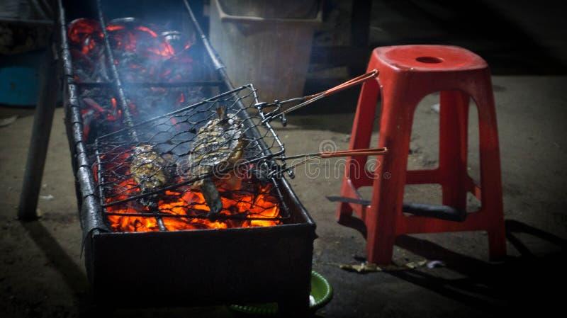 Una parrilla de los pescados en el mercado callejero tradicional con el carbón del resplandor de la quemadura imagenes de archivo