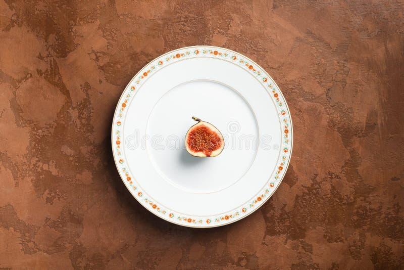 Una parte de fechas maduras en una placa blanca con un ornamento en un fondo texturizado marrón Concepto del alimento minimalism imágenes de archivo libres de regalías