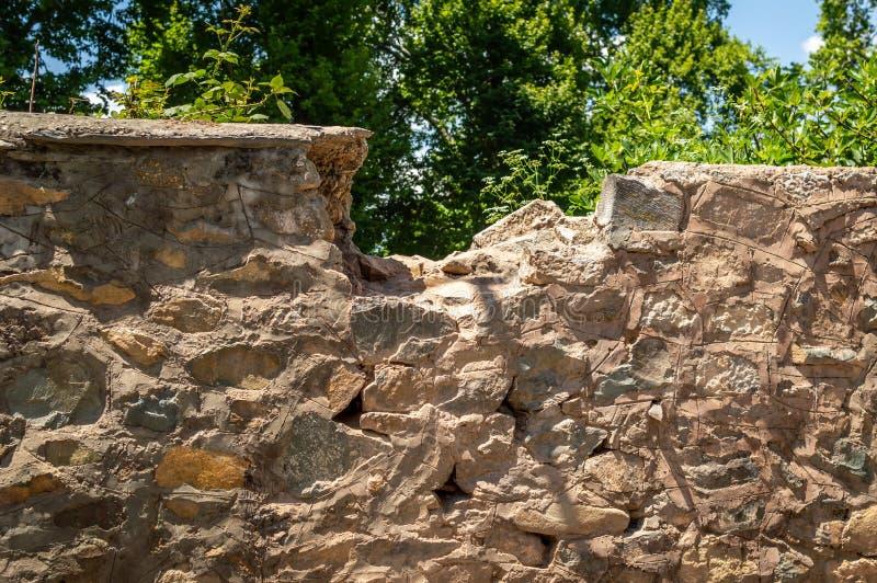 Una parte della cima di una parete di pietra è rotta fotografia stock