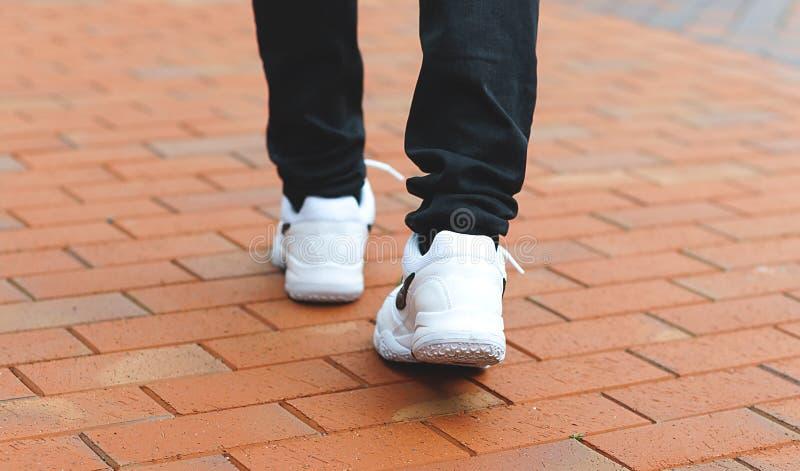 Una parte más inferior de las piernas masculinas en las zapatillas de deporte blancas fotografía de archivo