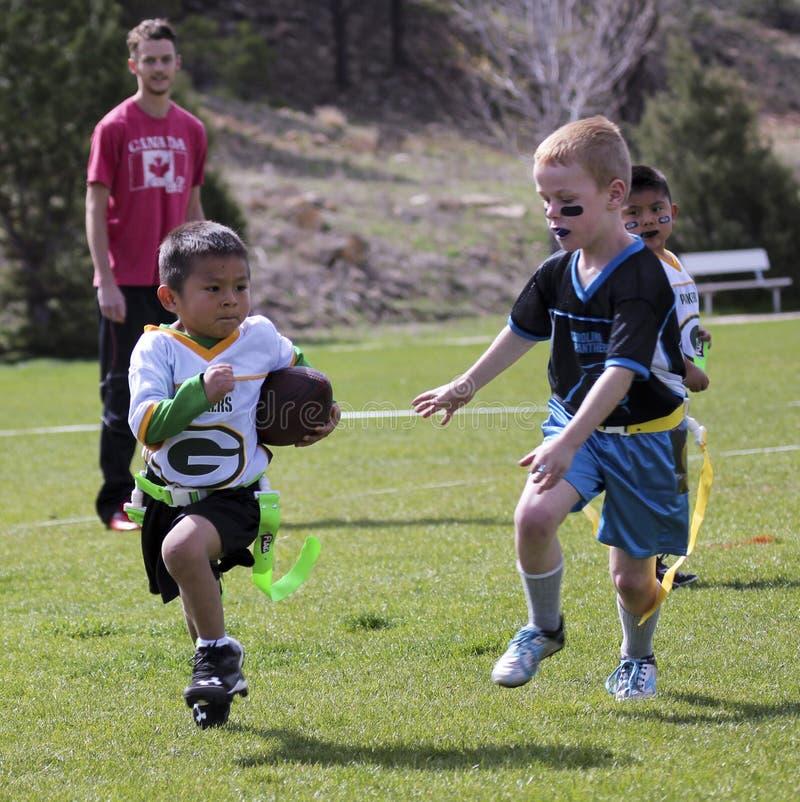 Una partita di football americano della bandiera per 5 ai bambini di 6 anni immagine stock libera da diritti