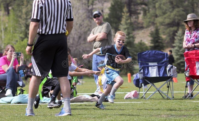 Una partita di football americano della bandiera per 5 ai bambini di 6 anni fotografia stock