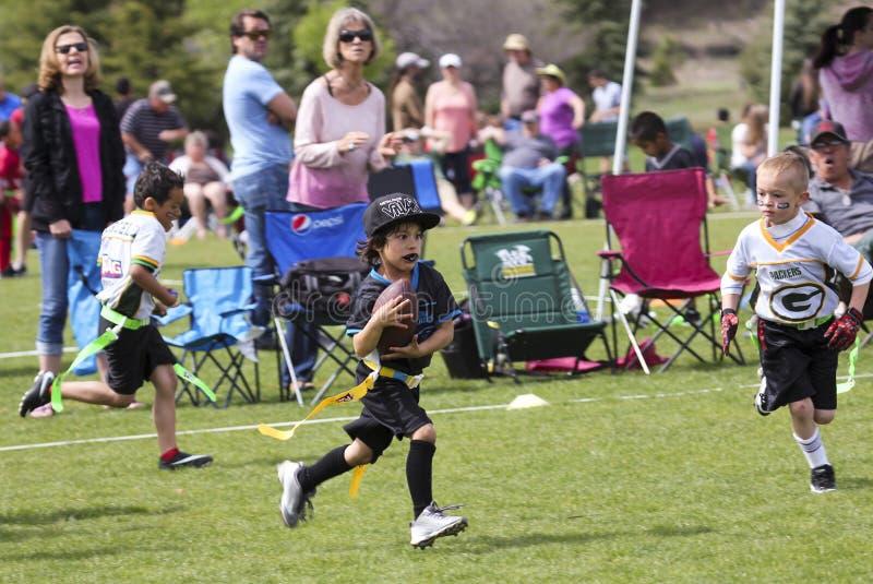 Una partita di football americano della bandiera per 5 ai bambini di 6 anni fotografia stock libera da diritti
