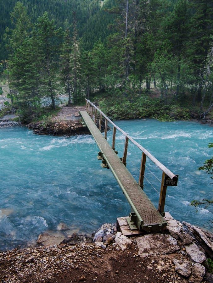 Una pasarela estrecha cruza encima el agua glacial azul en las montañas rocosas canadienses fotografía de archivo libre de regalías