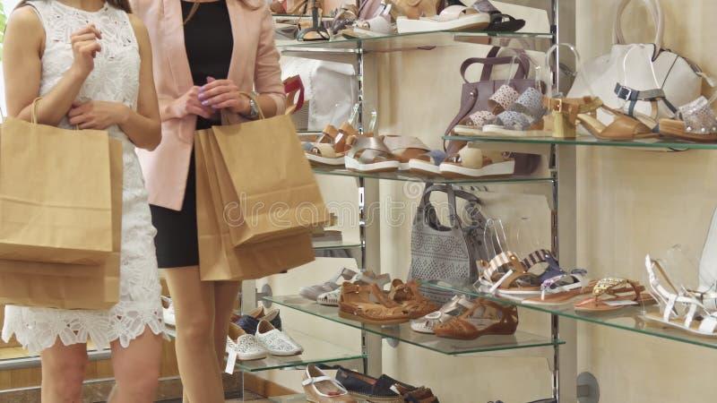 Una passeggiata di due donne al negozio di scarpe fotografia stock