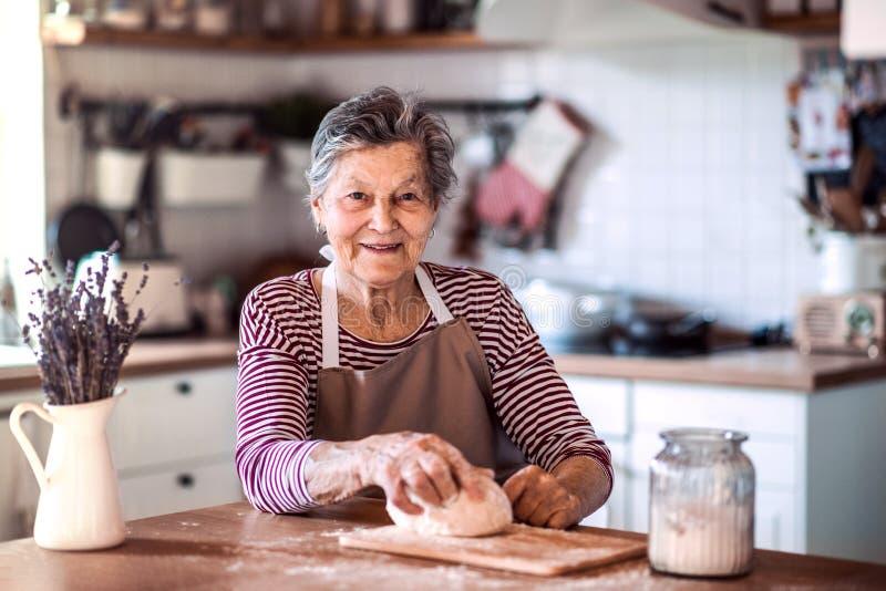 Una pasta d'impastamento della donna senior nella cucina a casa fotografia stock libera da diritti