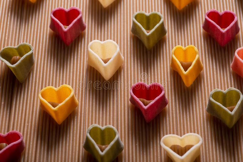 Una pasta in forma di cuore di 5 sapori del semolato di grano duro con le verdure sistemate su un fondo della pasta degli spaghet fotografia stock libera da diritti