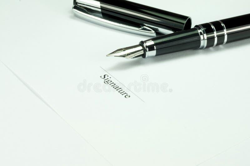 Una penna e una firma su un contratto fotografie stock