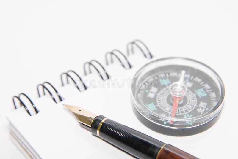 Una penna e una bussola sul taccuino fotografia stock