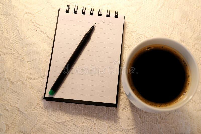 Una penna ritenuta verde si trova sopra un taccuino aperto Una tazza dei supporti freschi del caffè nero dal lato immagini stock libere da diritti