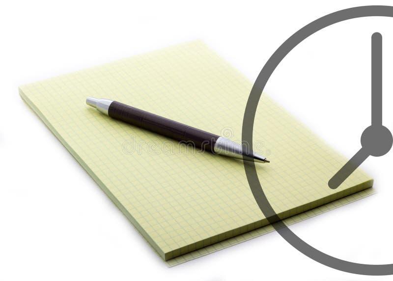 Una penna su un taccuino con un orologio per la fine di affari su fotografia stock libera da diritti