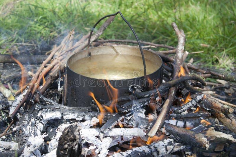 Una pentola d'acqua viene riscaldata su un fuoco fatto di rami immagini stock