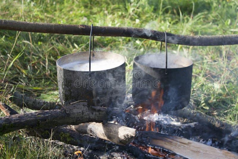 Una pentola d'acqua viene riscaldata su un fuoco fatto di rami fotografia stock libera da diritti