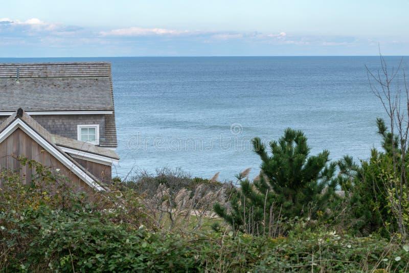 Una pequeña cabaña, arbustos verdes y arbustos, contra el horizonte azul en el fondo, Block Island, RI, los E.E.U.U. foto de archivo