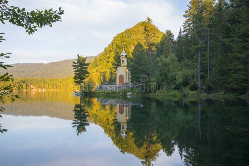 Una pequeña capilla cristiana se coloca en la orilla del lago del bosque imagen de archivo