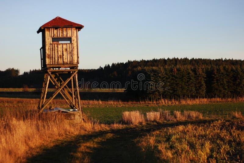 Una pequeña casa en un campo en la puesta del sol fotos de archivo