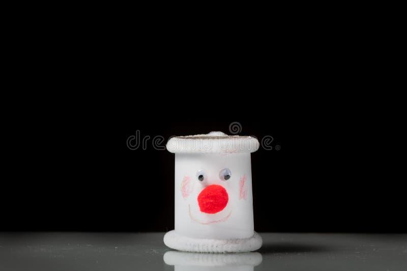 Una pequeña figura de un muñeco de nieve hecho de un rollo del papel higiénico por un niño imágenes de archivo libres de regalías