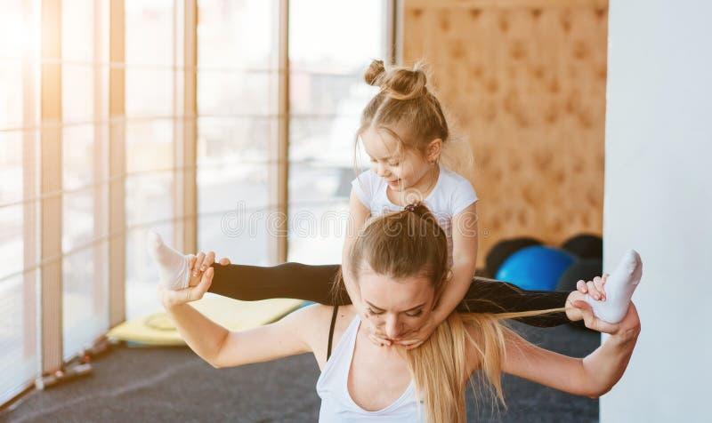Una pequeña hija se sienta en su parte posterior del ` s de la madre imagen de archivo