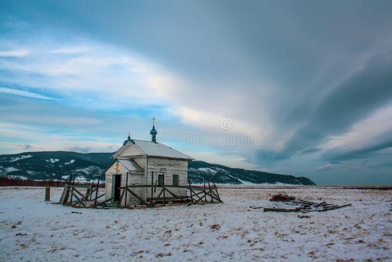 Una pequeña iglesia cristiana de madera se coloca entre las nieves y las montañas imagen de archivo libre de regalías
