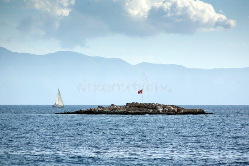 Una pequeña isla rocosa con una bandera de Turquía Además de los flotadores del barco de navegación Travesía azul encendido fotos de archivo