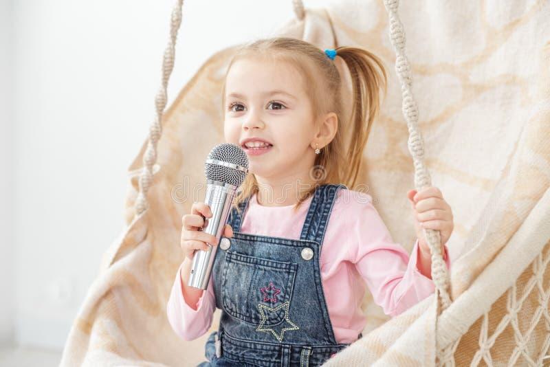 Una pequeña muchacha alegre canta una canción en el micrófono La estafa fotografía de archivo libre de regalías