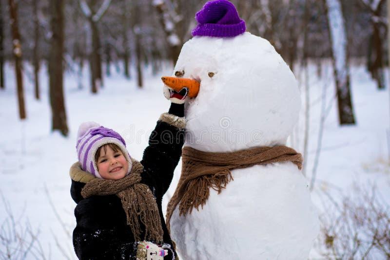 Una pequeña muchacha alegre sostiene una zanahoria grande, la nariz de un muñeco de nieve grande foto de archivo libre de regalías