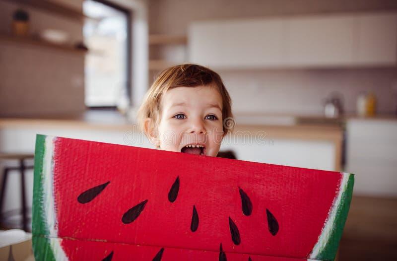 Una peque?a muchacha con la fruta de papel grande del juguete en casa, comiendo concepto de la fruta fotografía de archivo libre de regalías