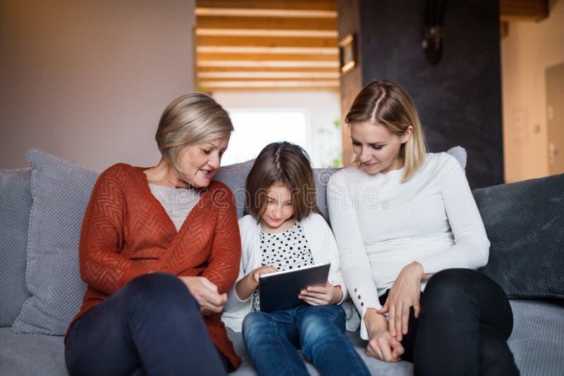 Una pequeña muchacha con la madre y la abuela en casa imágenes de archivo libres de regalías