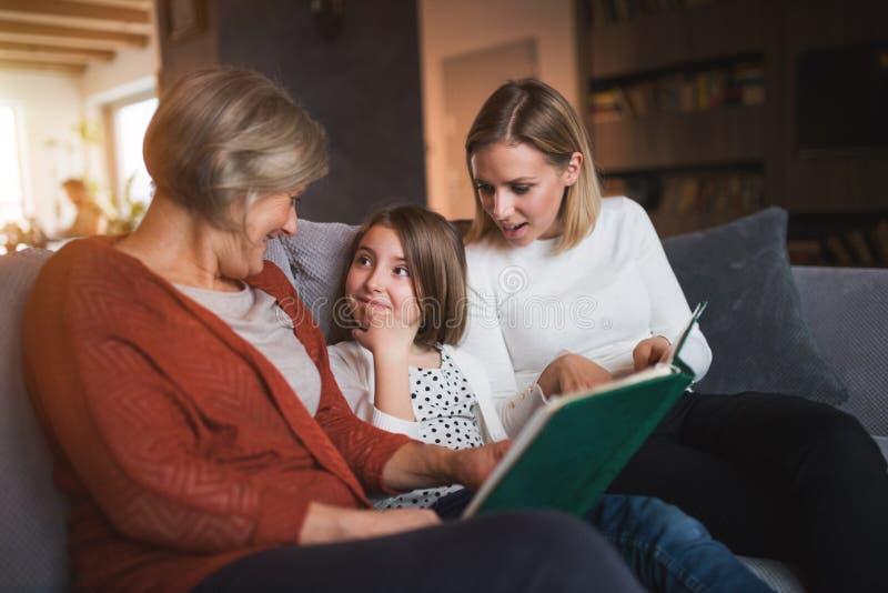 Una pequeña muchacha con la madre y la abuela en casa foto de archivo libre de regalías