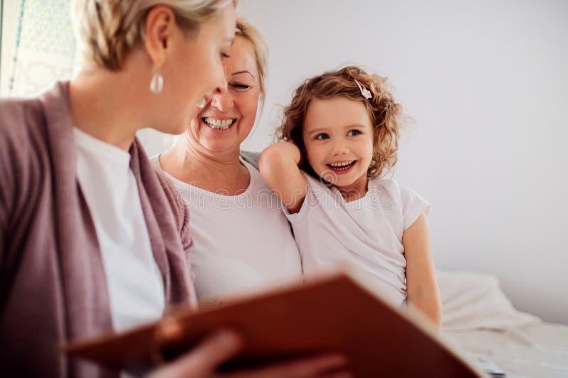 Una pequeña muchacha con la madre y la abuela en casa, mirando las fotografías imagenes de archivo