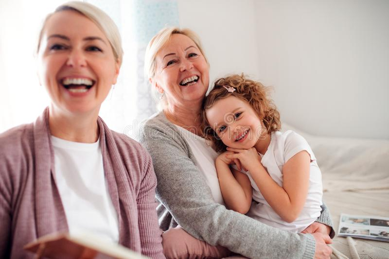 Una pequeña muchacha con la madre y la abuela en casa, riendo fotografía de archivo