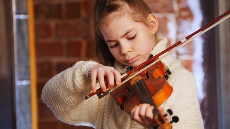 Una pequeña muchacha concentrada en el suéter blanco que toca el violín foto de archivo libre de regalías