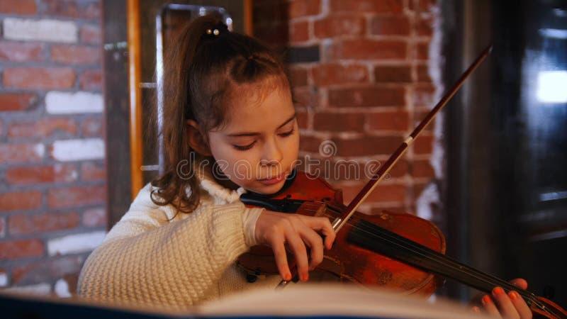 Una pequeña muchacha concentrada en el suéter blanco que toca el violín por las notas en el estudio fotografía de archivo libre de regalías