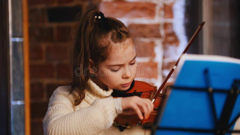 Una pequeña muchacha concentrada en el suéter blanco que toca el violín por las notas fotos de archivo