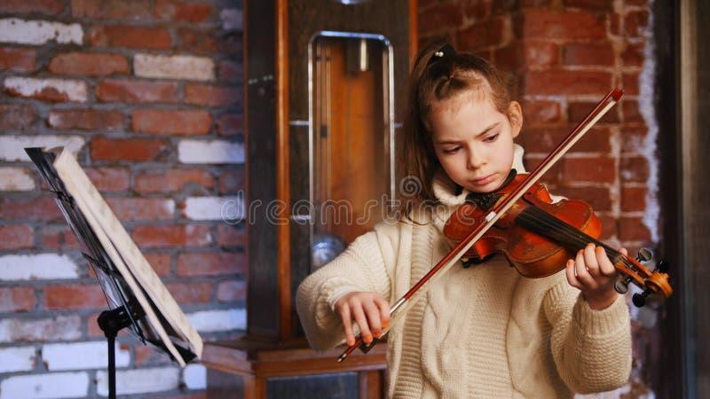 Una pequeña muchacha concentrada en el suéter que toca el violín por las notas fotografía de archivo