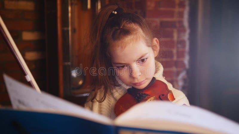 Una pequeña muchacha concentrada que toca el violín por las notas imagen de archivo