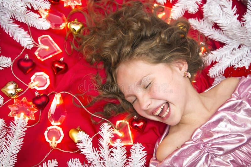 Una pequeña muchacha de pelo rubio que miente en un piso rojo con una guirnalda de la Navidad y ramas del abeto alrededor de su c fotografía de archivo libre de regalías