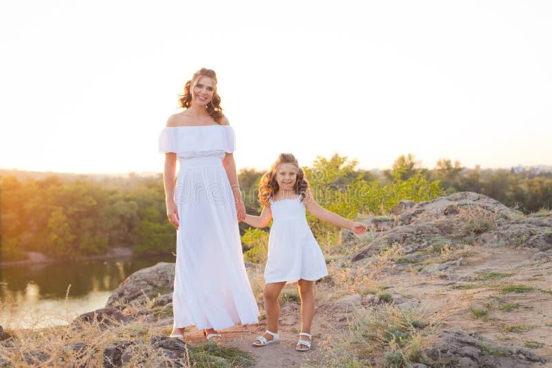 Una pequeña muchacha de risa sonriente con el pelo marrón rizado vistió el vestido corto blanco con la madre hermosa joven en bla foto de archivo