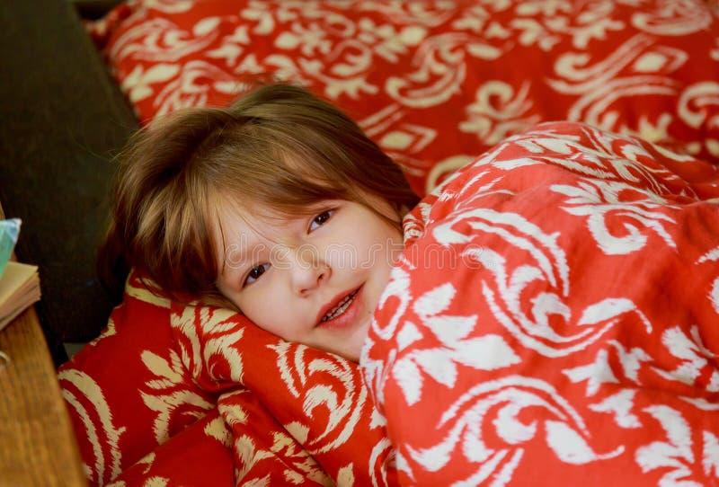 Una pequeña muchacha enferma en el dormitorio Niña sentando en llevar de la cama los pijamas imagen de archivo libre de regalías