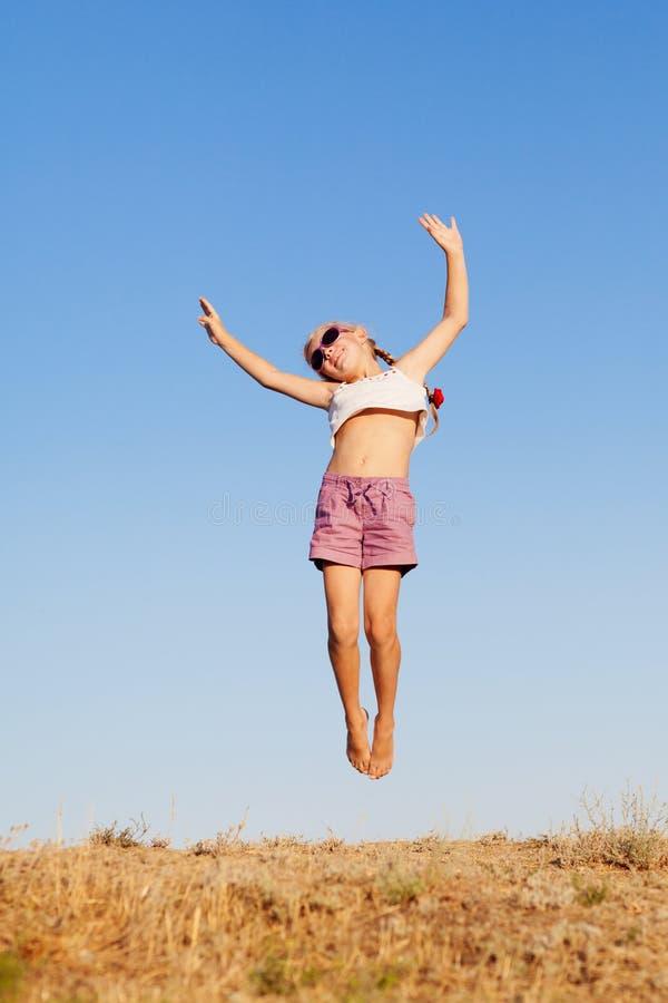 Una pequeña muchacha feliz que salta al aire libre imagenes de archivo