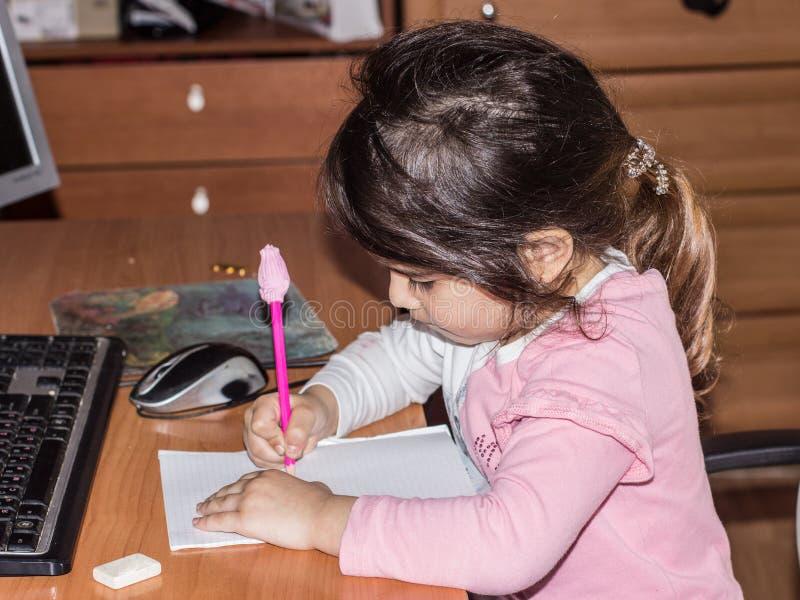 Una pequeña muchacha hermosa está dibujando en una hoja de papel en el escritorio del ordenador retrato del primer de una muchach fotografía de archivo libre de regalías