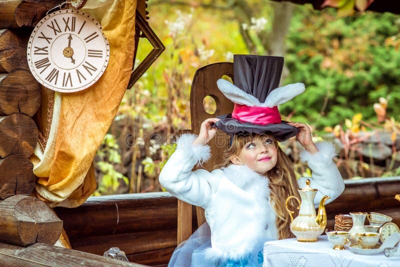 Una pequeña muchacha hermosa que sostiene el sombrero del cilindro con los oídos le gusta un conejo de arriba en la tabla foto de archivo