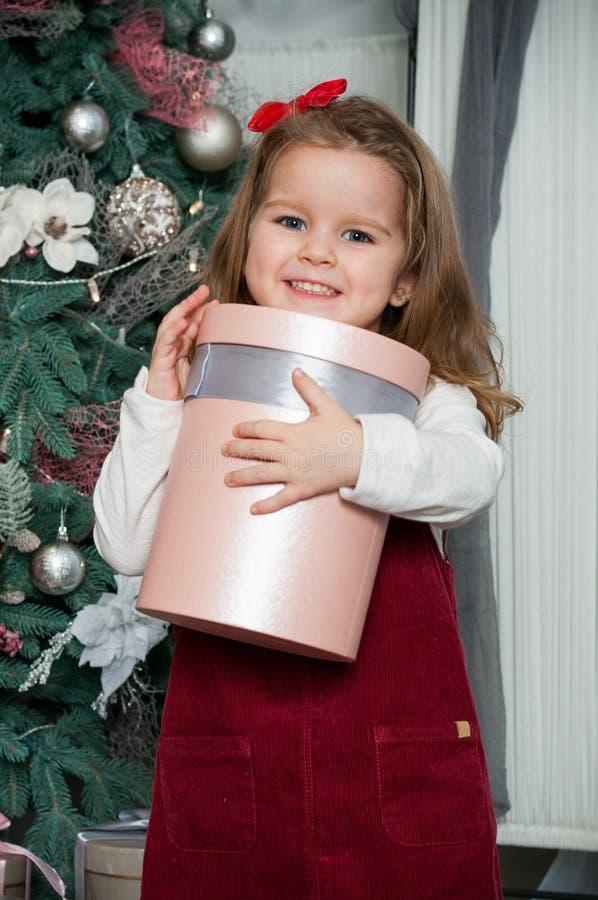 Una pequeña muchacha linda caucásica que sonríe con la actual caja en su mano en el cuarto festivo del estudio del Año Nuevo imagen de archivo