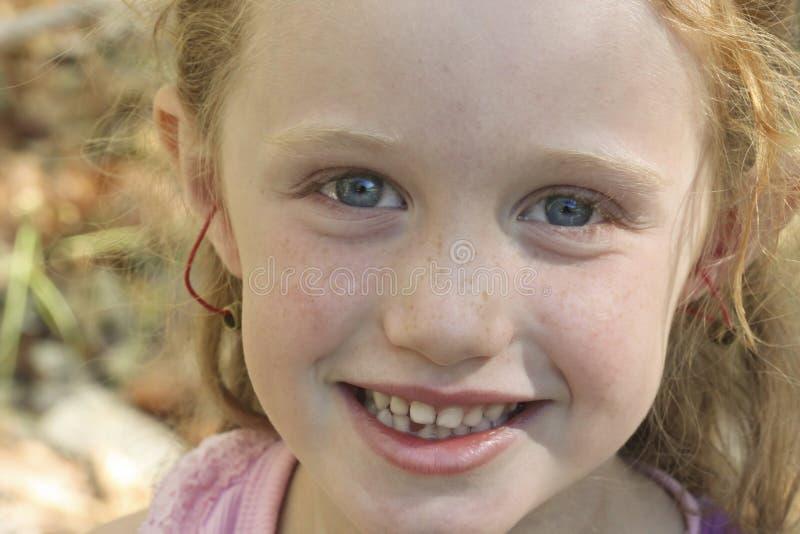 Una pequeña muchacha pelirroja con los ojos azules imagen de archivo
