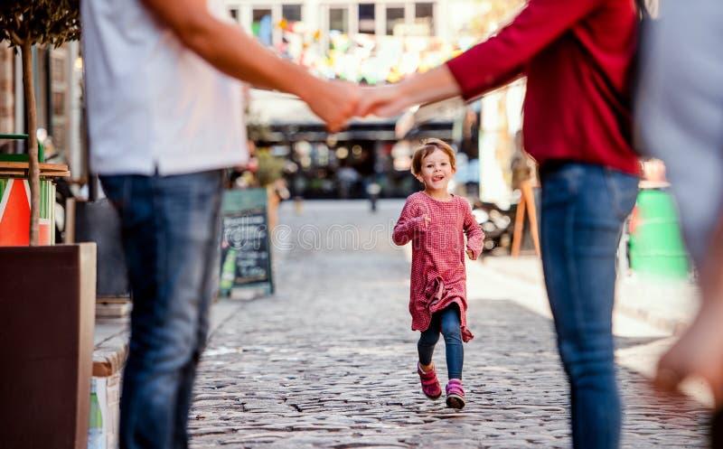 Una pequeña muchacha que corre hacia padres irreconocibles al aire libre en ciudad imagen de archivo