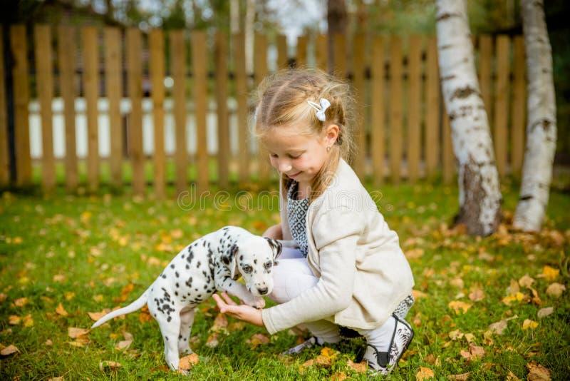 Una pequeña muchacha rubia con sus outdooors del perro casero en parque La niña linda está jugando con su perrito en el parque ve fotos de archivo libres de regalías
