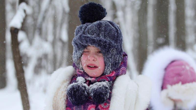 Una pequeña muchacha trastornada con nieve en su cara foto de archivo
