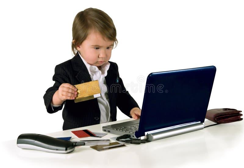 Una pequeña niña (muchacho) con el teléfono, tarjeta del ordenador y de crédito foto de archivo