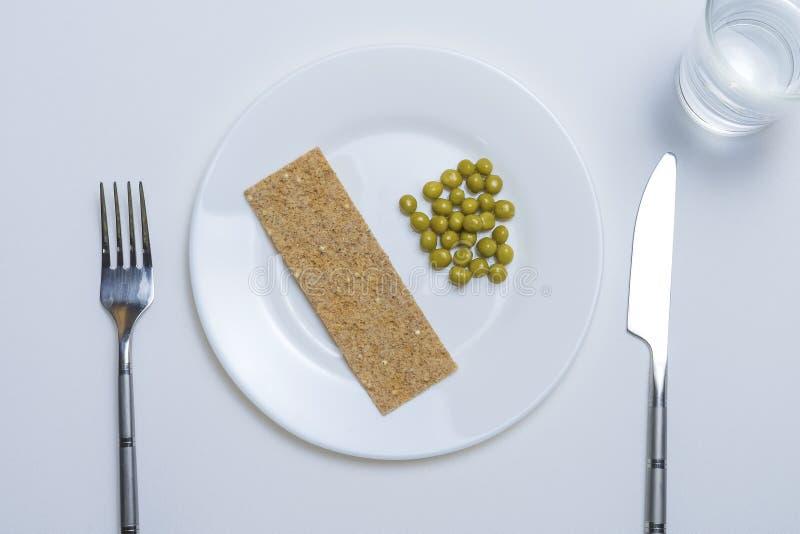 Una pequeña porción de comida en una placa grande en un primer blanco de la tabla fotografía de archivo libre de regalías